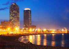Beach and towers of Port Olimpic in twilight. Barcelona. View of Somorrostro Beach and towers of Port Olimpic in summer twilight in Barcelona, Spain Royalty Free Stock Image