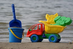 Beach toys. Children's toys on sand on a background water Royalty Free Stock Image