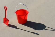 Beach toys. A red plastic bucket and spade on the beach royalty free stock photography