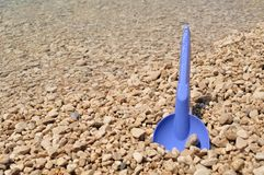 Beach toys - blue shovel on the beach Stock Photos