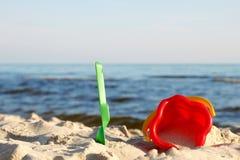 Beach toys. A bucket and spade on a beach Stock Images