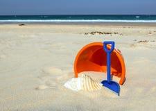 Beach toys. Orange bucket, blue spade and seashell on sunny sandy beach background stock photos