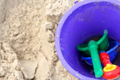 Beach toys in the sand. Blue Bucket and shovels in the sand royalty free stock photos