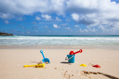 Beach toys in the sand. Background of some toys for playing in the sand at a beach with blue sky royalty free stock image
