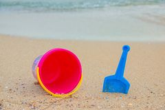 Beach toys on sand. Bright bucket, shovel on the sand. And a little water at top of frame. Sunny day stock images