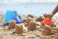 BEACH TOYS AND SAND CASTLES. Summer fun building sand castle on beach Royalty Free Stock Image