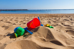 Beach toys in sand on sea shore Royalty Free Stock Images