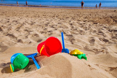 Beach toys in sand on sea shore Stock Photo