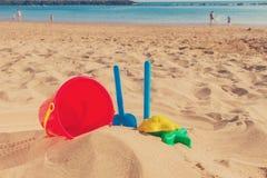 Beach toys in sand on sea shore Royalty Free Stock Photos
