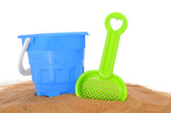 Beach toys on the sand. Toy shovel and beach pail on the sand on a white background Royalty Free Stock Image