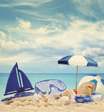 Beach toys on sandy beach with blue sea Stock Image