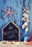 Beach toys, seashells, starfishes and text school holidays. A house-shaped chalkboard with the text schools out surrounded by different beach toys, seashells and stock image