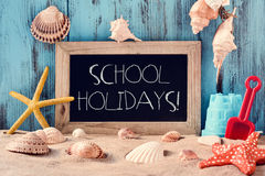 Beach toys, seashells, starfishes and text school holidays. A wooden-framed chalkboard with the text school holidays surrounded by different beach toys Royalty Free Stock Photos