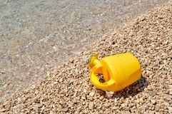 Beach toys - yellow watering can on the beach Stock Photo