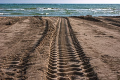 Beach tracks. Tyre tracks run across a sandy beach on a sunny summer day Stock Photography