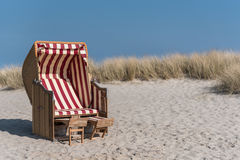 Beach. Traditional canopied beach chair at baltic sea with marram grass an blue sky in background Royalty Free Stock Photo