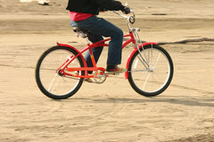 Beach transportation. A guy pedals his new retro look bike down the beach Royalty Free Stock Image