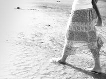 Woman walking on sand beach. Closeup detail of female feet .Step up concept. Beach travel - Black and white woman walking on sand beach. Closeup detail of Stock Photography