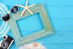Beach travel concept mock up with frame and surrounding accessories on blue wood. Beach travel concept mock up with frame and surrounding accessories on a blue royalty free stock photography
