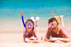 Beach travel couple having fun snorkeling, lying on summer beach sand with snorkel equipment Royalty Free Stock Photos