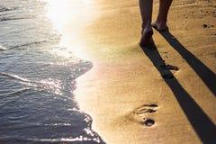 Beach travel - legs walking on sandy beach leaving footprints in Stock Photo