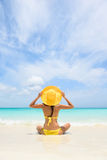 Beach Travel Vacation Holidays Woman Relaxing. Woman sitting on sea shore during summer. Rear view of female wearing yellow sunhat and bikini. Carefree tourist royalty free stock photography