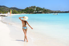 Beach travel woman bikini wearing sun hat walking Stock Image