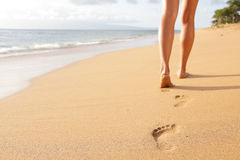 Beach travel - woman walking on sand beach closeup. Beach travel - woman walking on sand beach leaving footprints in the sand. Closeup detail of female feet and Royalty Free Stock Images