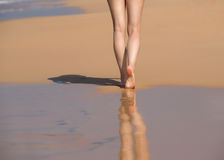 Beach travel - woman walking on sand beach leaving footprints in Stock Photos