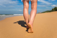 Beach travel - woman walking on sand beach leaving footprints in Royalty Free Stock Photography