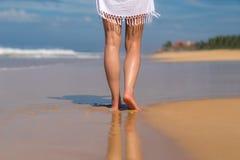 Beach travel - woman walking on sand beach leaving footprints in Stock Photo