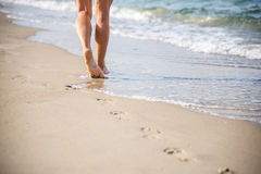Beach travel - woman walking. Woman walking on sand beach leaving footprints in the sand royalty free stock photo