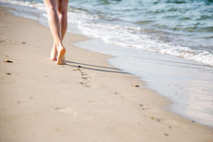 Beach travel - woman walking. Woman walking on sand beach leaving footprints in the sand stock photos