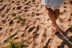 Beach Travel woman walking on a sandy  leaving footprints in the sand. Close up detail of female legs and golden   the Royalty Free Stock Photo