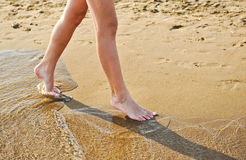 Beach travel - young girl walking on sand beach leaving footprints in the sand. Closeup detail of female feet and golden sand. Teenage female,walking down the stock photo