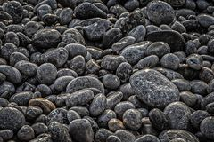 The beach treasure. A lot of  irregular stones bathed by sea water on the beach at the Chios Island in Greece Stock Image