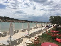 Beach Trogir Croatia. Blue skies with a view from beach to Trogir Croatia with sun loungers and umbrellas Royalty Free Stock Photo