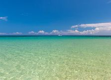 Beach on tropical island. Clear blue water and sky Stock Image