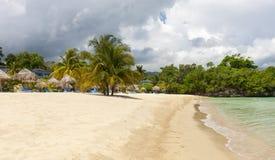 Beach on tropical island. Clear blue water and sky Stock Photos