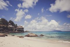 Beach of a tropical island with white sand and blue ocean. On a hot Sunny day. Blue sky. On the shore a few small houses Stock Photography
