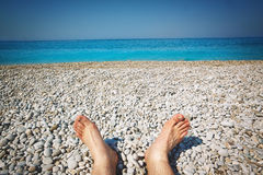 Beach and tropical sea. Traveler sits on a background of the sea with sunbathers feet Stock Image
