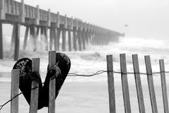 Beach during tropical storm. Flip flops on fence at beach by pier during tropical storm Royalty Free Stock Photo