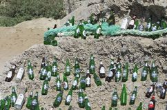 Beautifully laid out empty beer bottles on a huge boulder in a sunny weather. The beach of Tsampika, Rhodes island, Greece - September 21, 2017: Beautifully Stock Photography