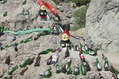 Beautifully laid out empty beer bottles on a huge boulder in a sunny weather. The beach of Tsampika, Rhodes island, Greece - September 21, 2017: Two figures of Stock Images