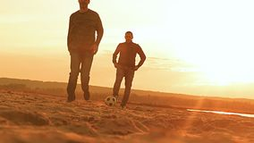 On the beach two men playing ball, slow motion video. At sunset on the beach two men playing soccer ball in slow motion video stock footage