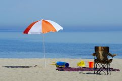Beach Umbrella. A beach scene with colourful umbrellas, beach toys, beach blanket, and beach chair Royalty Free Stock Images