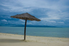 Beach umbrella. A lonely umbrella in a peaceful place near the beautiful sea under the cloudy sky Stock Photo