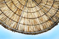Beach umbrella. Crop of beach straw umbrella against blue sky Stock Images