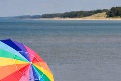 Beach with Umbrella. Lake Michigan coast line with colorful beach umbrella Stock Photo