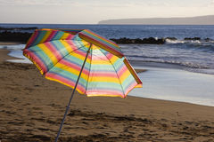 Beach Umbrella. A bright striped umbrella at the beach in the late afternoon sun Stock Photo